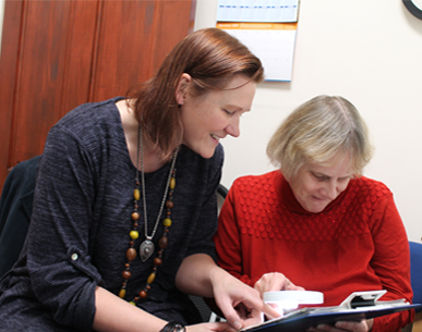 A younger woman helping an older woman to read through a magnifying glass