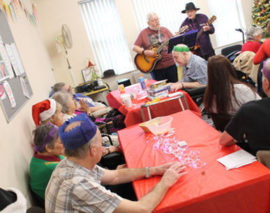 A Christmas social event with people sat eating and a band playing songs